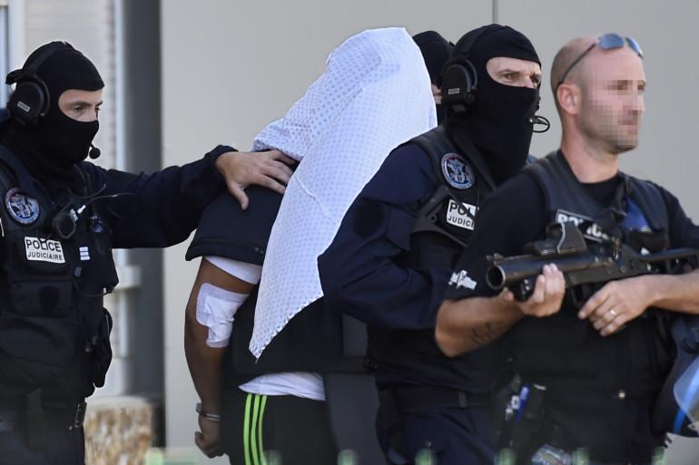 Yassin Salhi escorté par des policiers devant son immeuble de Saint-Priest, près de Lyon, le 28 juin 2015.