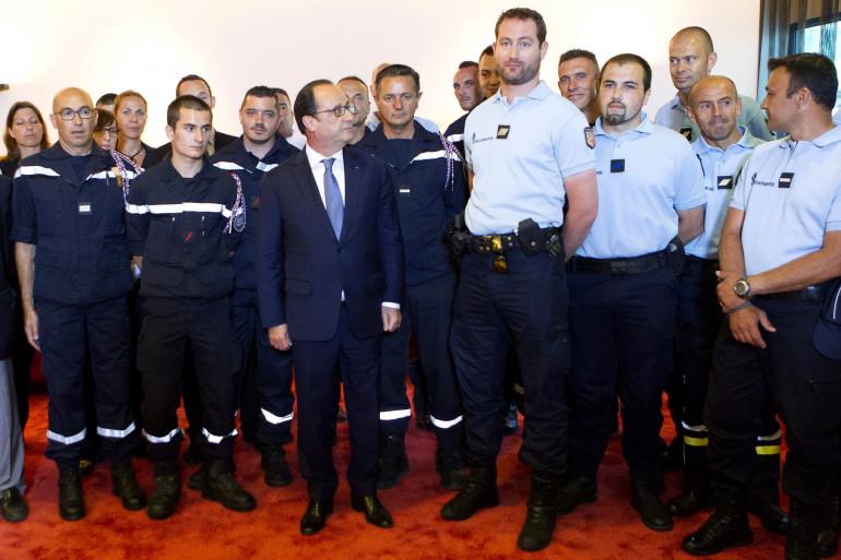 François Hollande entouré des forces de sécurité intervenues lors de l'attentat en Isère, à Lyon le 1er juillet 2015.