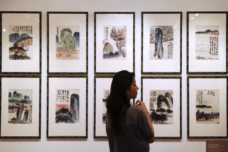 Une femme devant les œuvres de l'artiste Qi Baishi, un artiste copié et revendu par Xiao Yuan, le 6 octobre 2010.