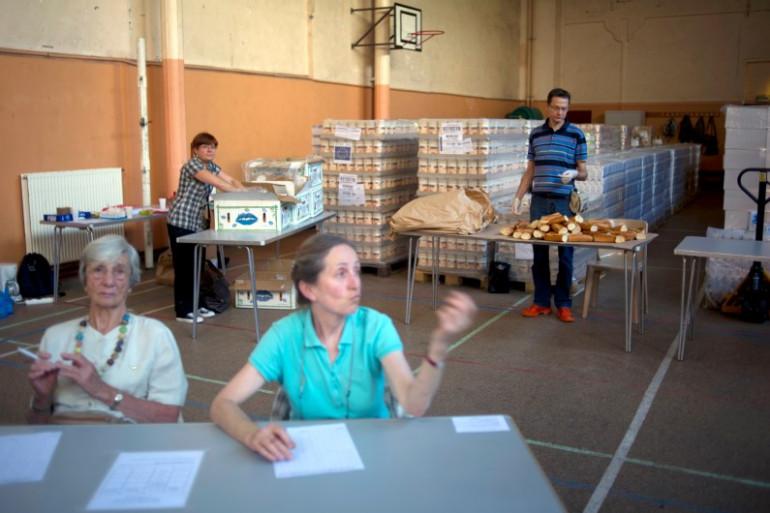 Des bénévoles de l'association Août Secours Alimentaire (ASA) prennent en charge des familles lors d'une distribution de colis repas, le 01 août 2011, à Paris (illustration).