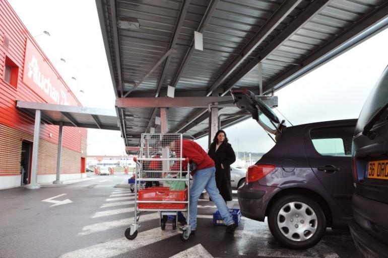 Un employé d'une enseigne de supermarché charge les courses d'une cliente dans son véhicule