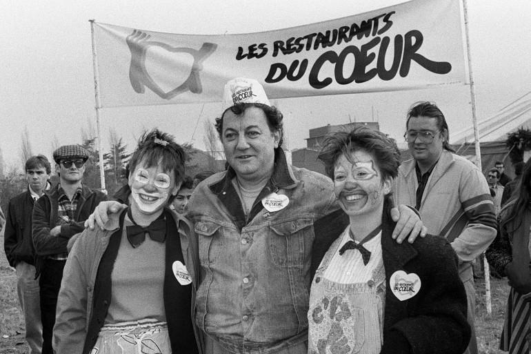Coluche, entouré de deux femmes déguisées en clown, pose devant l'entrée de l'un des trois restaurants du coeur de la région parisienne, le 21 décembre 1985