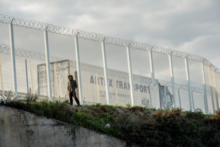 """Un migrant marche le long de la barrière près de la """"jungle"""" de Calais, le 25 septembre 2015."""