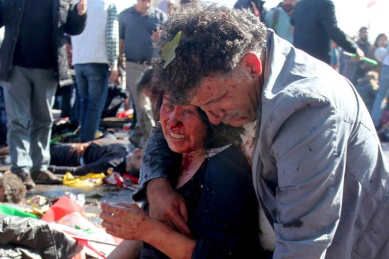 Un homme réconforte une femme blessée lors de l'attaque meurtrière dans la gare d'Ankara en Turquie, le 10 octobre 2015.