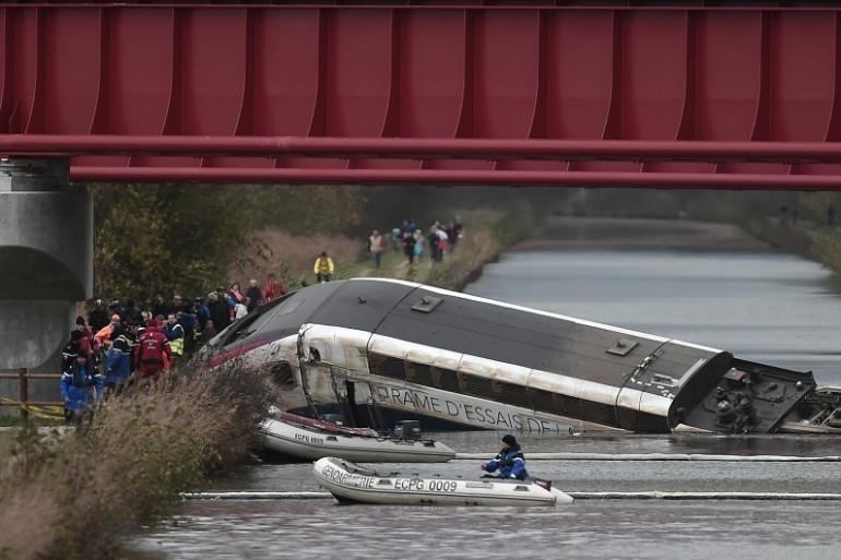 Les secouristes interviennent à Eckwersheim, après qu'un TGV a déraillé, une partie étant tombée dans le canal.