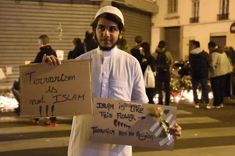 """""""Le terrorisme, ce n'est pas l'islam, le terrorisme n'a pas de religion"""", disent ces pancartes portées par un musulman venu rendre hommage aux victimes du bistrot"""