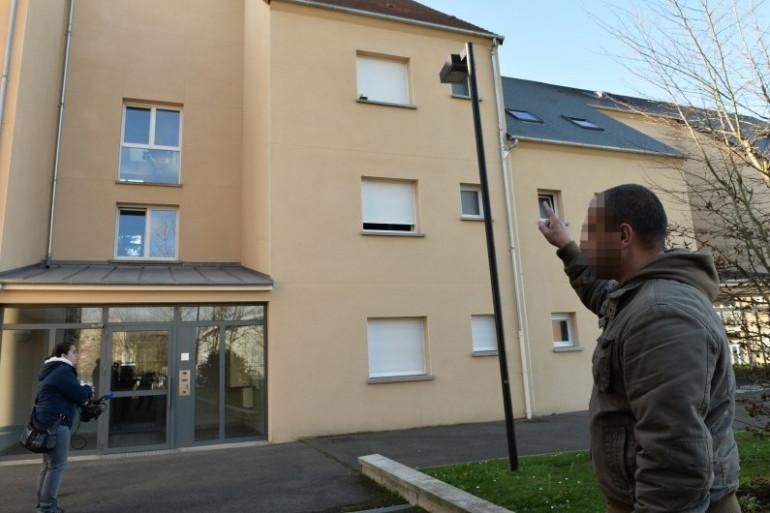 Un homme pointant l'appartement dans lequel a vécu Fabien Clain à Alençon
