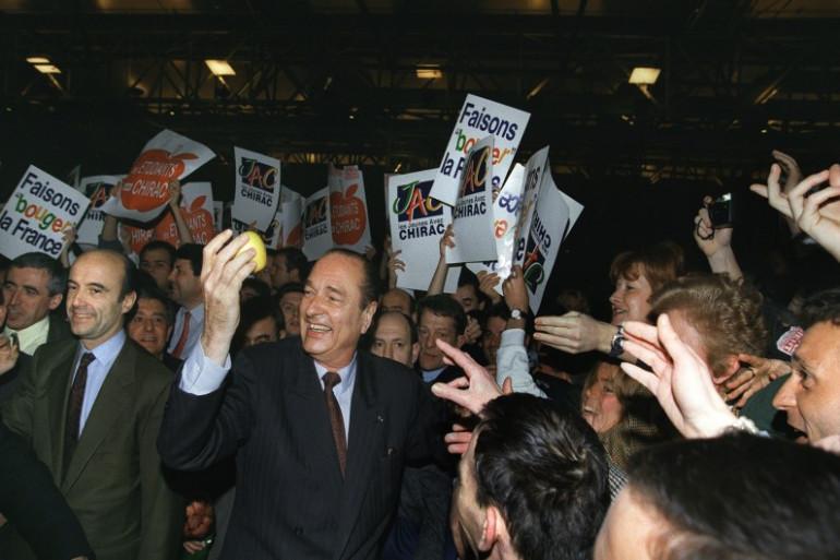 Jacques Chirac entouré de militants lors de la campagne présidentielle le 24 mars 1995. Il est accompagné d'Alain Juppé, son directeur de campagne
