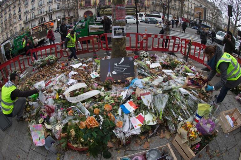 Des agents de la Propreté de Paris récoltent certains hommages déposés autour du Bataclan, le 10 décembre 2015