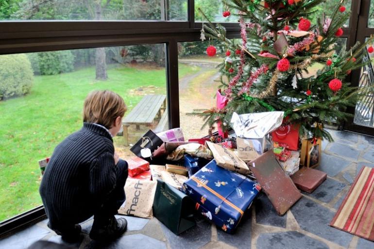 Un enfant s'apprêtant à ouvrir ses cadeaux de Noël