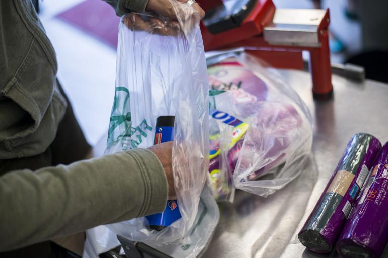 Une personne remplit un sac plastique dans un supermarché