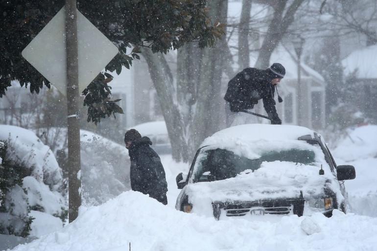 """Des riverains tentent d'enlever la neige de leurs véhicules en Virginie après le passage de la tempête """"Jonas""""."""