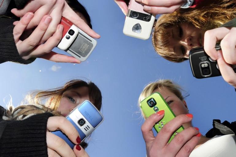 Des jeunes filles consultant leurs portables (illustration)