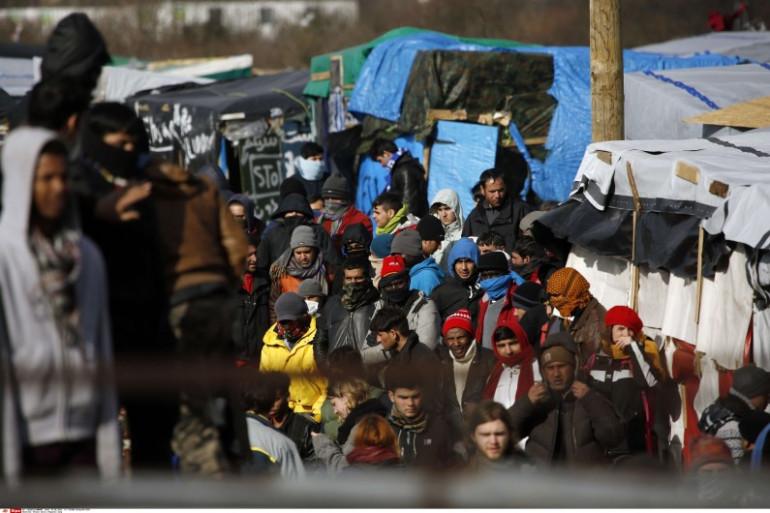 """Des migrants quittent la """"jungle"""" de Calais dans le nord de la France."""