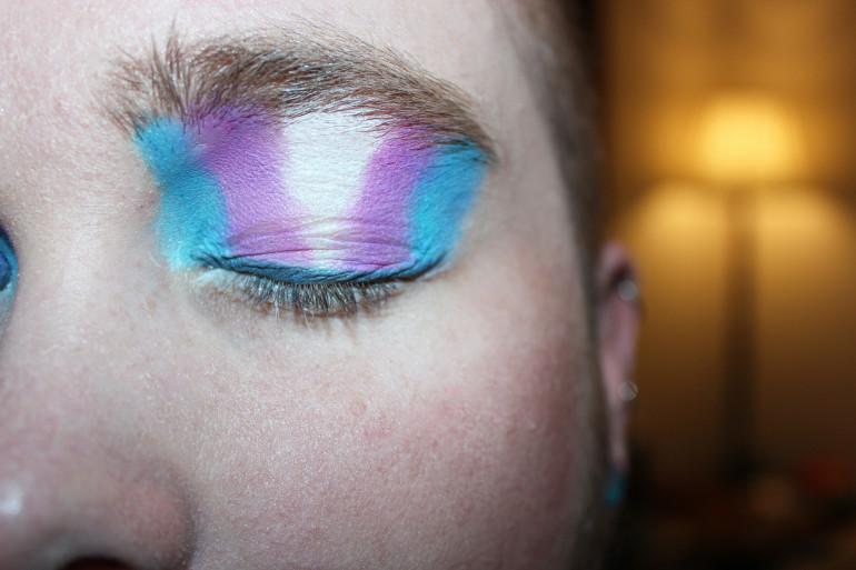 Une personne maquillée aux couleurs du drapeau trans (illustration).