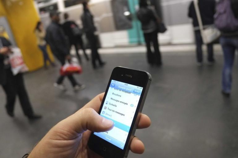 Une personne consulte son smartphone dans le métro à Paris