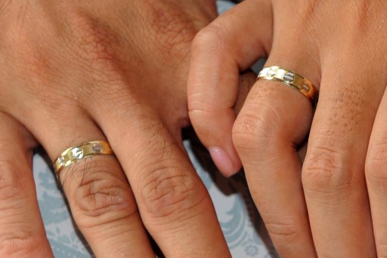 Un couple de jeunes mariés portant des alliances (illustration)