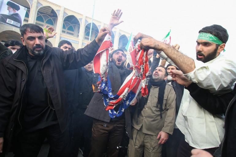 """Des Iraniens brûlent un drapeau américain lors d'une manifestation contre les """"crimes"""" américains à Téhéran le 3 janvier 2020 après le meurtre du général de division Qasem Soleimani lors d'une frappe américaine."""