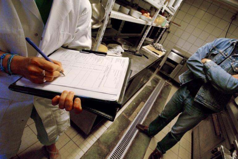 Un inspecteur sanitaire visite les cuisines d'un restaurant de la côte normande, le 23 juillet 2004