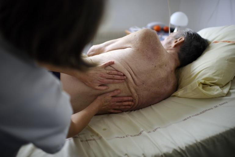 Une kinésithérapeute masse un patient à l'hôpital (illustration)