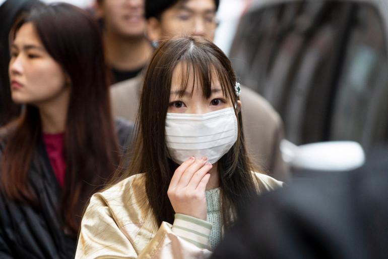 Une jeune femme portant un masque chirurgical pour se protéger du coronavirus.