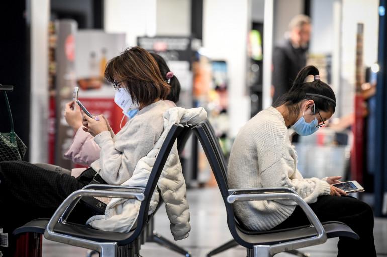Des passagers portent des masques de protection à l'aéroport Charles-de-Gaulle.
