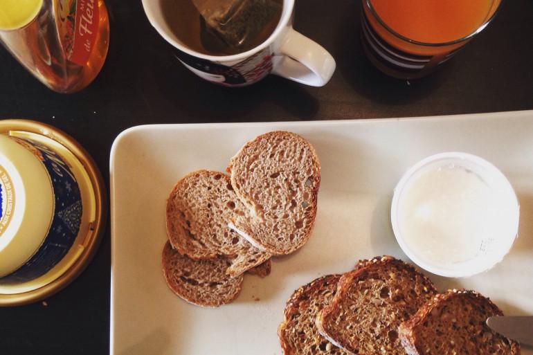 Un petit déjeuner complet : pain complet, thé, jus de fruit 100% et laitage