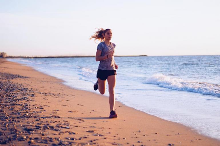 Une femme courant sur la plage (illustration).