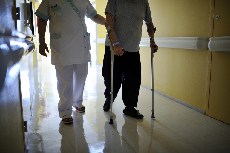 Une aide-soignante aide un homme à marcher au CHU d'Angers le 23 octobre 2013 (Illustration).