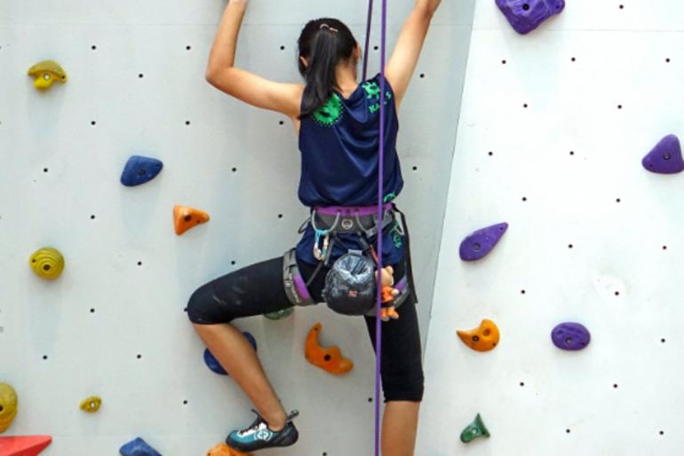 Jeune femme sur un mur d'escalade (Illustration).
