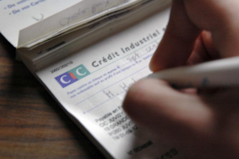 Le titulaire d'un compte au CIC remplit un chèque le 30 décembre 2005 à Paris.