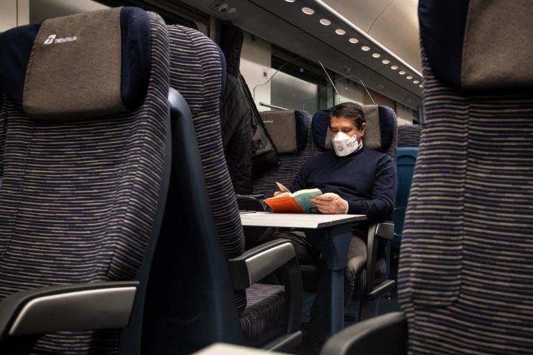 Un voyageur qui porte un masque dans un train (Illustration)