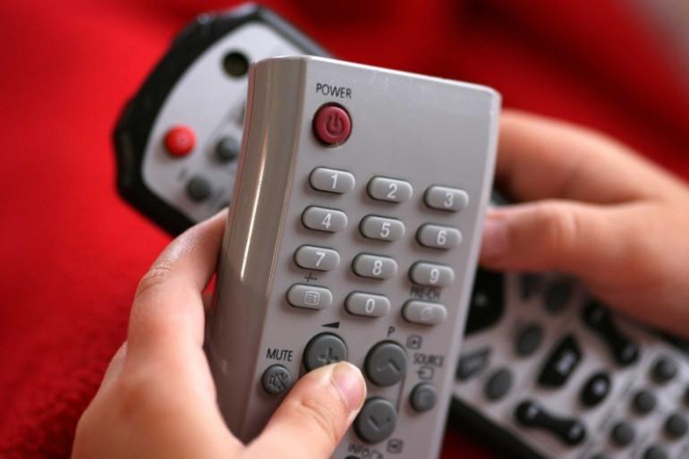 Une personne tient des télécommandes (illustration)