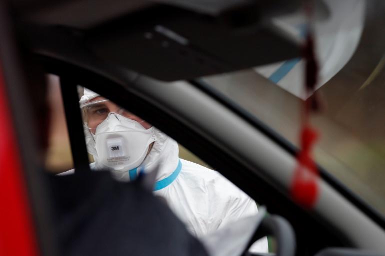 Un automobiliste à un point de contrôle de température, pendant l'épidémie de coronavirus.