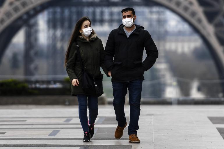 Deux personnes masquées sur l'esplanade devant la Tour Eiffel
