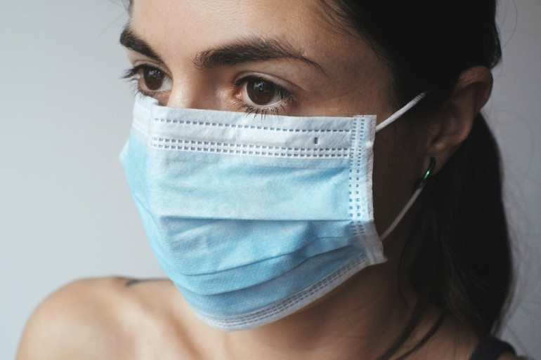 Une femme portant un masque chirurgical (Image d'illustration).
