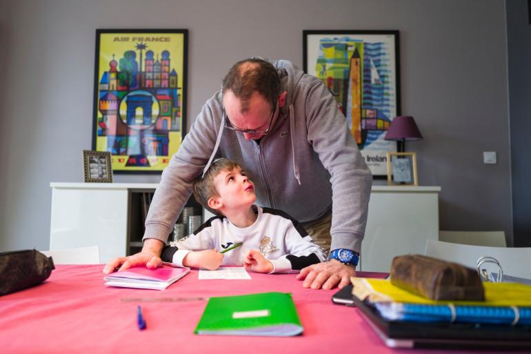 Un père et son fils pendant une séance d'école à la maison à Mulhouse