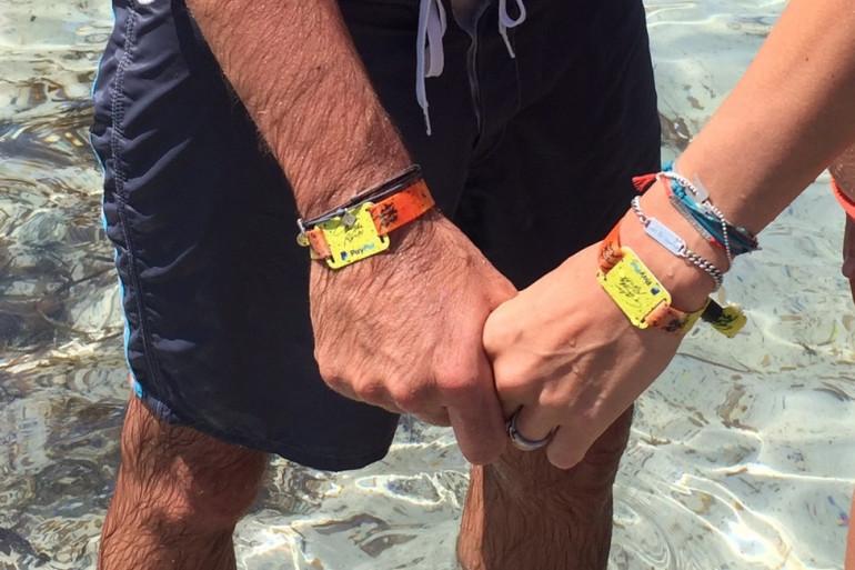 Des festivaliers portent le bracelet cashless au festival Calvi on the rocks en juillet 2016