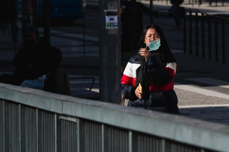 Une femme retirant son masque chirurgical à Stockholm le 6 avril 2020