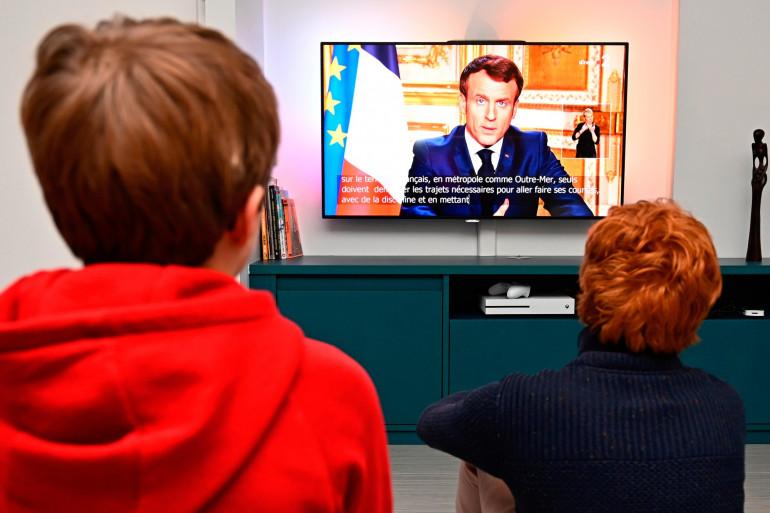 Un garçon et sa mère regarde une allocution présidenteille d'Emmanuel Macron le 16 mars 2020 à Rennes