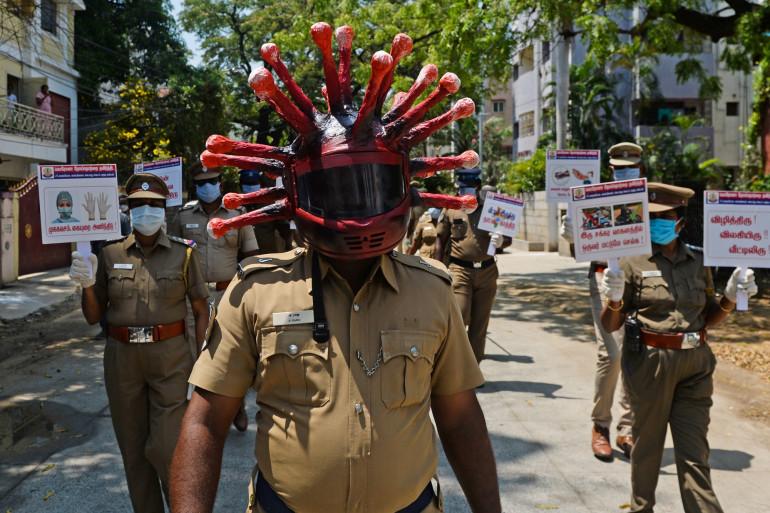 Un policier avec un masque en forme de virus pour inciter les populations à rester confinées, à Chennai (Inde), le 12 avril 2020