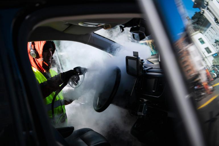 Un homme désinfecte son taxi en Suède.