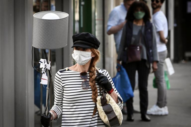 Une femme tranporte une lampe à Paris le 25 avril 2020