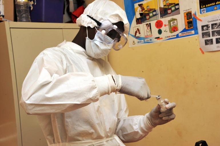 Une femme prépare le vaccin contre Ebola VSV-EBOV qu'elle s'apprête à administrer, en Guinée, le 10 mars 2015.