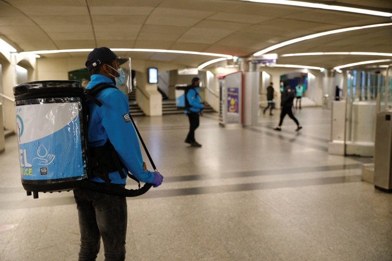 Des agents RATP distribue du gel hydroalcoolique dans les couloirs du métro le 11 mai