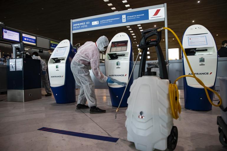 Un agent d'entretien nettoie une machine à l'aéroport de Roissy le 14 mai 2020