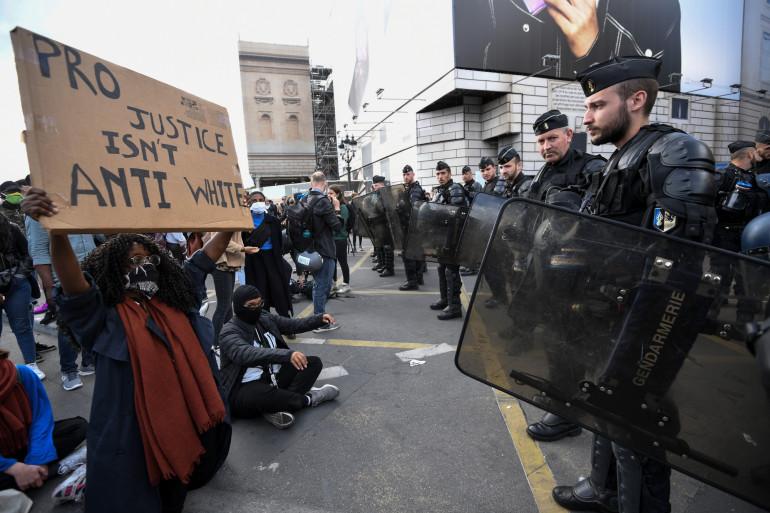 Une manifestante tient sa pancarte face aux policiers lors de la manifestation contre les violences policières à Paris, samedi 6 juin.