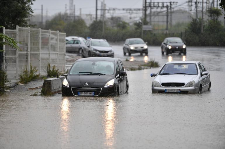 Des voitures roulent sous la pluie (illustration)