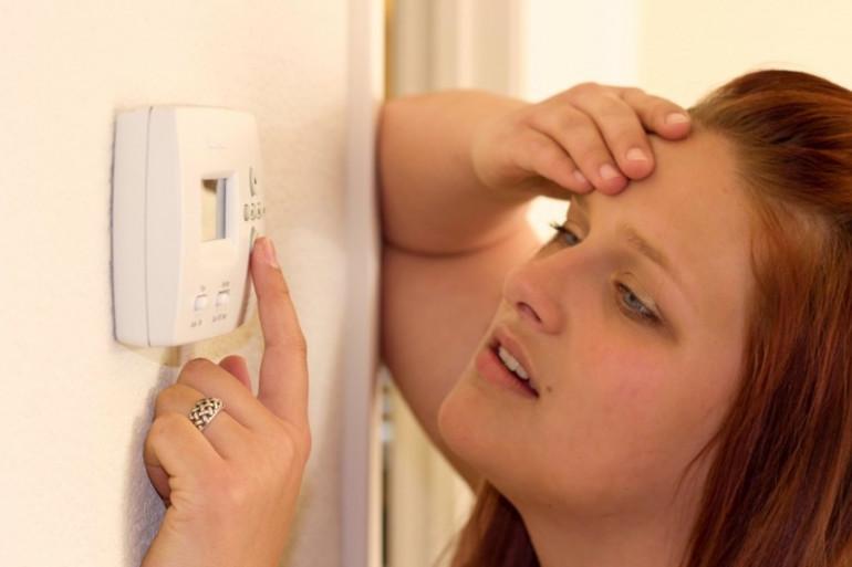 Une femme règle son système de climatisation (illustration)