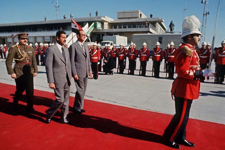 Le Premier ministre Jacques Chirac et le président irakien Saddam Hussein passent en revue la garde d'honneur de l'armée irakienne lors de l'arrivée de Chirac à Bagdad en janvier 1976.